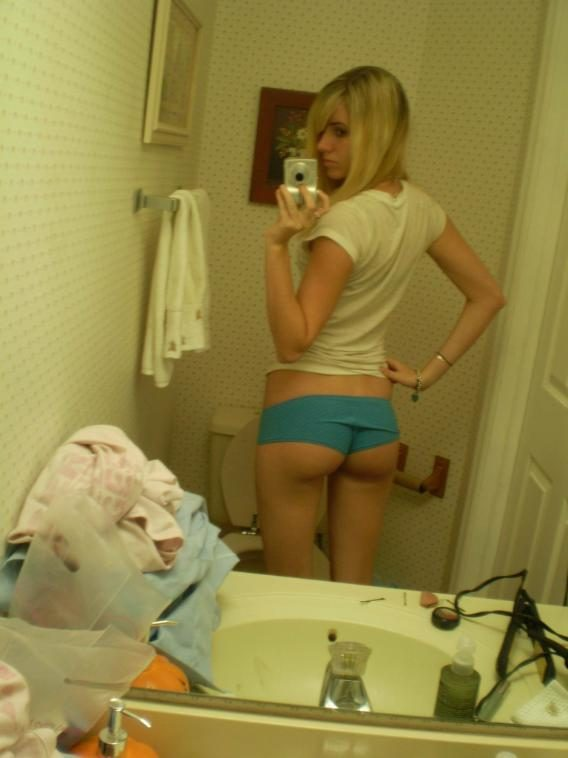 Blonde girlfriend taking pictures in the mirror