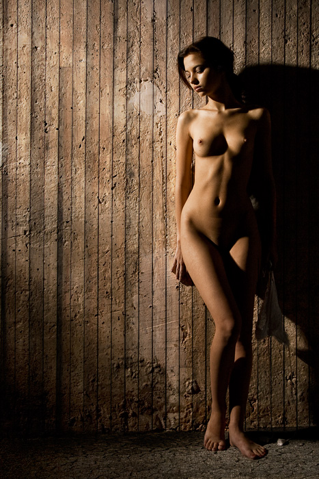 Nude beauty standing against a wall