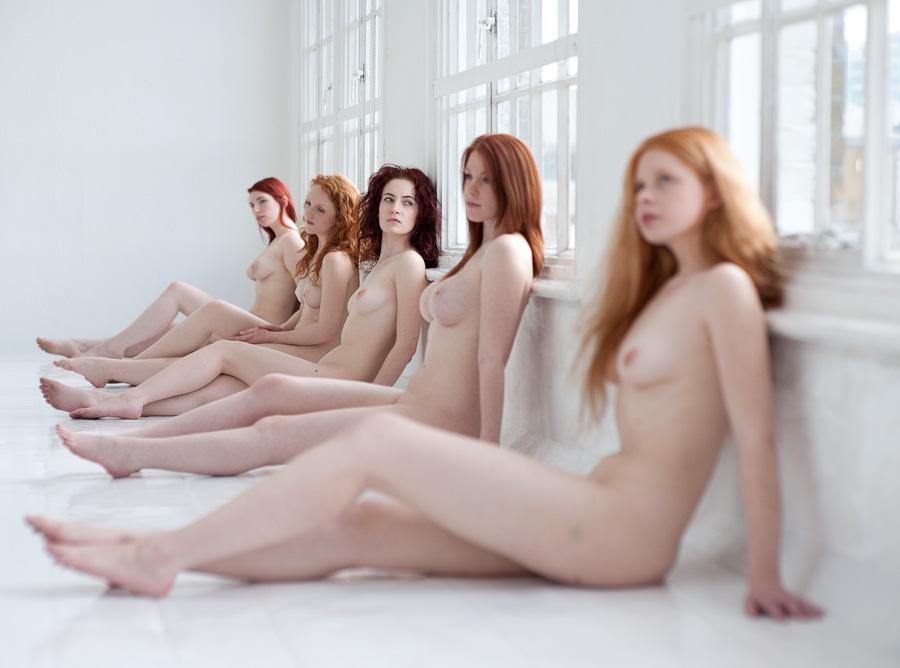 Nude pale redhead girl standing against the wall