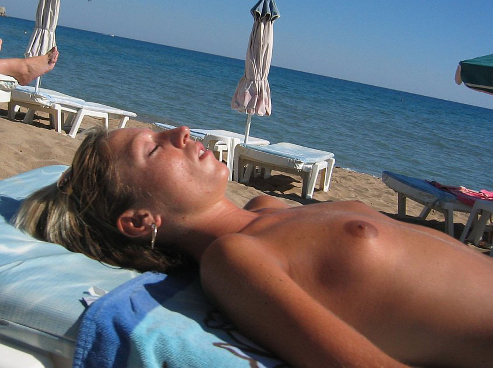 Tanning blond beauty exposed topless