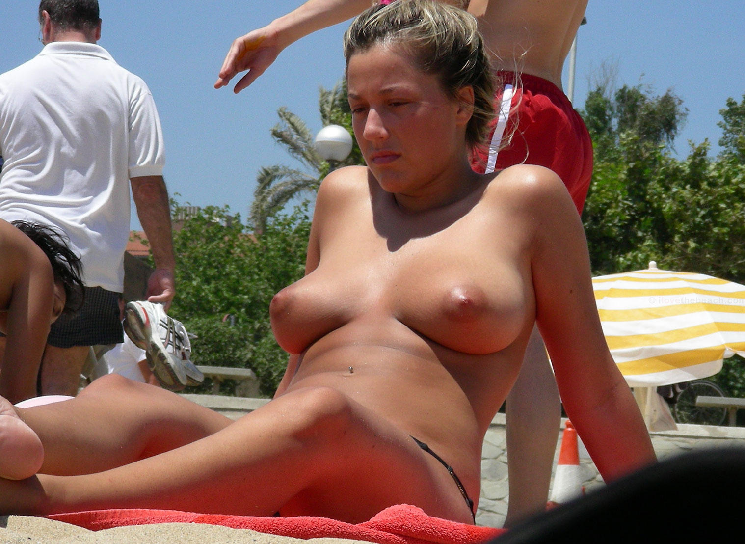 Topless beauty tanning and showing her round boobs