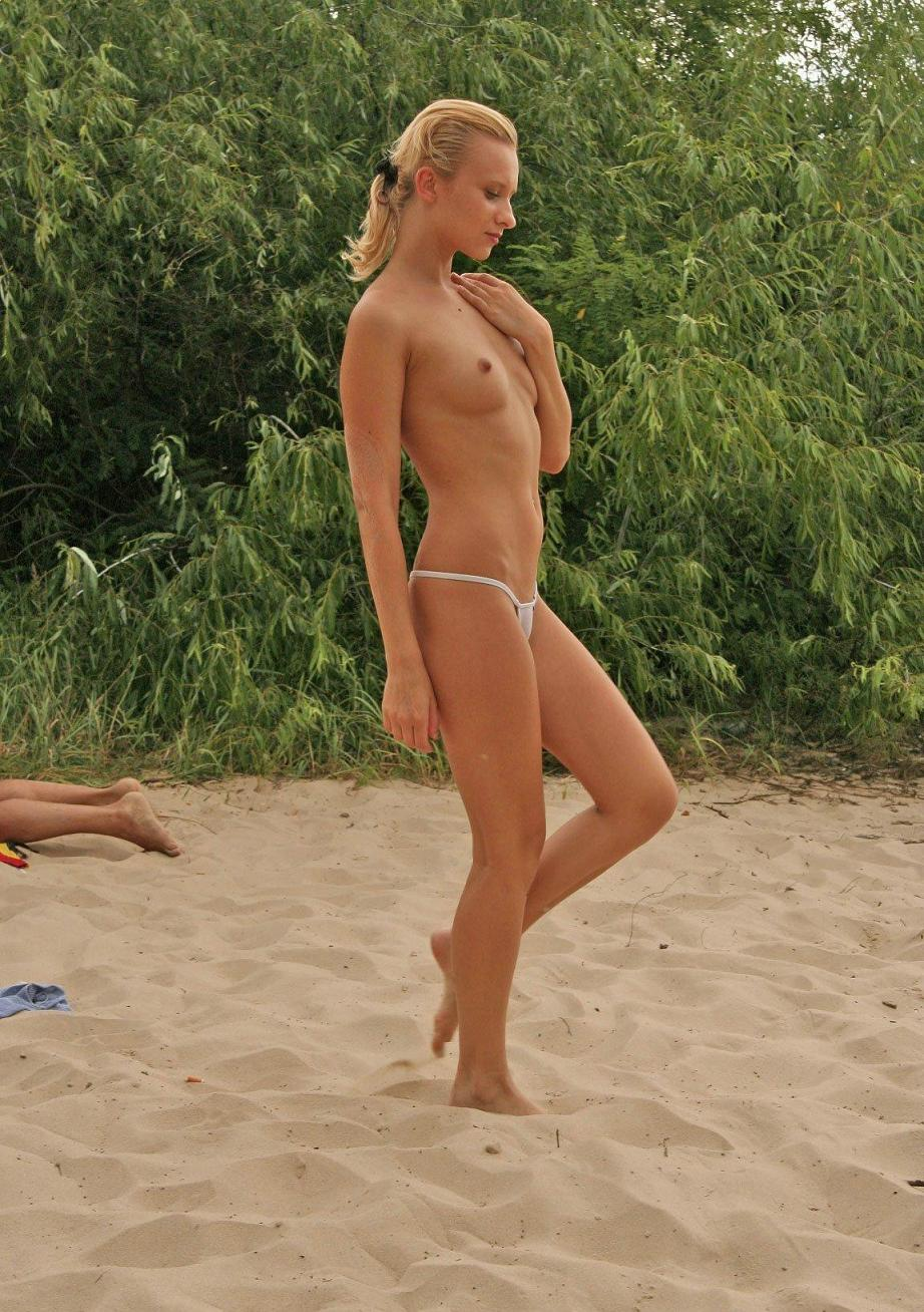 Topless chick on an exotic beach showing her assets