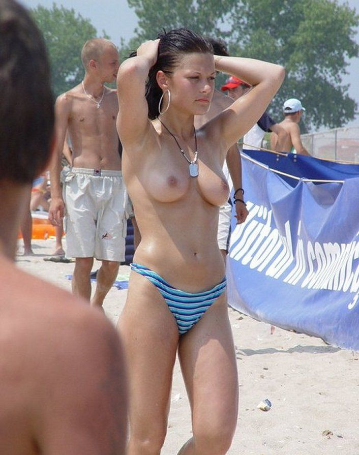Gorgeous chick walking topless on the beach