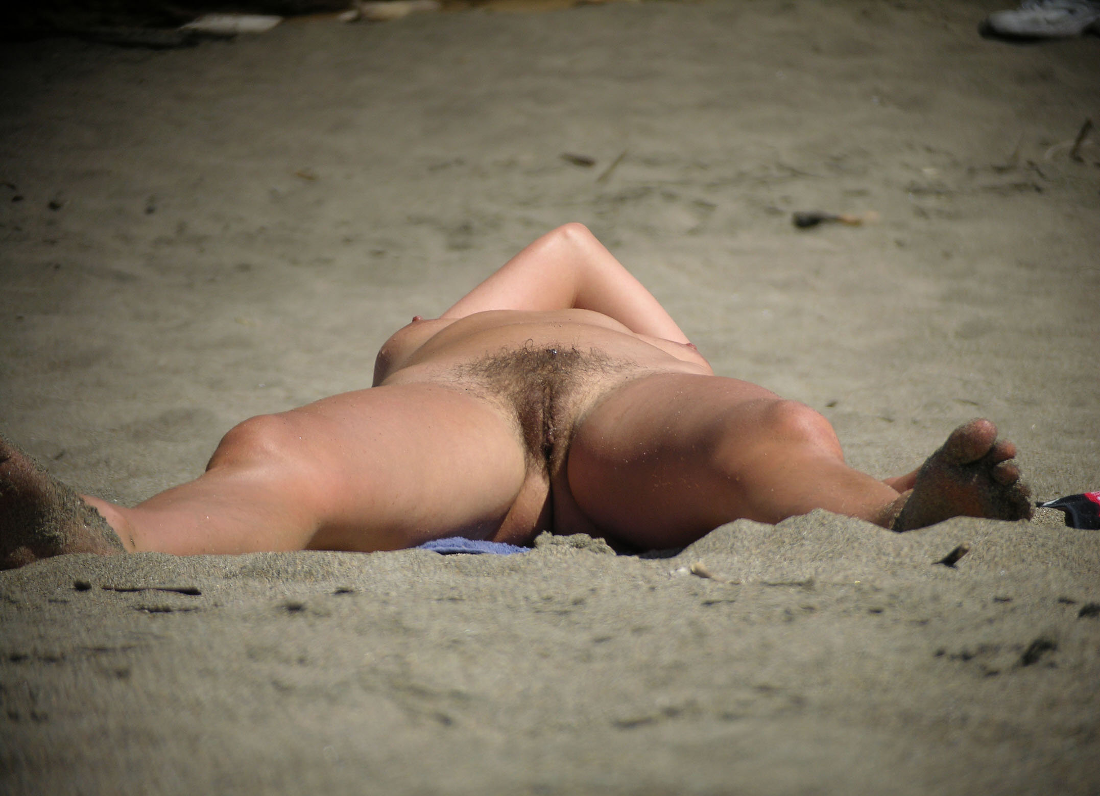 Sexy cougar exposing her hairy cunt on beach