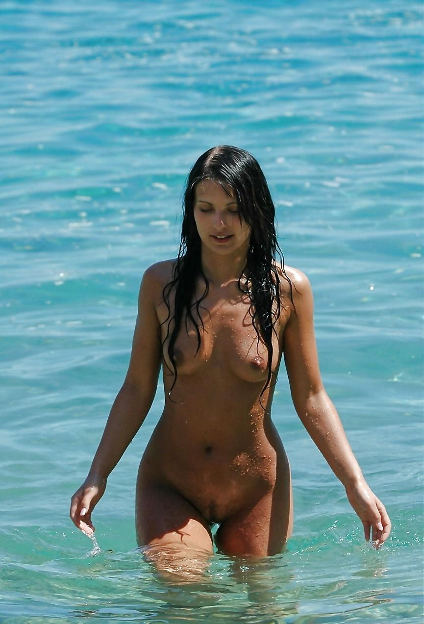 Foxy brunette playing naked in the ocean