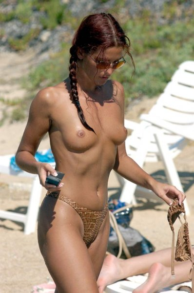 Sexy bronzed redhead strutting along the beach topless