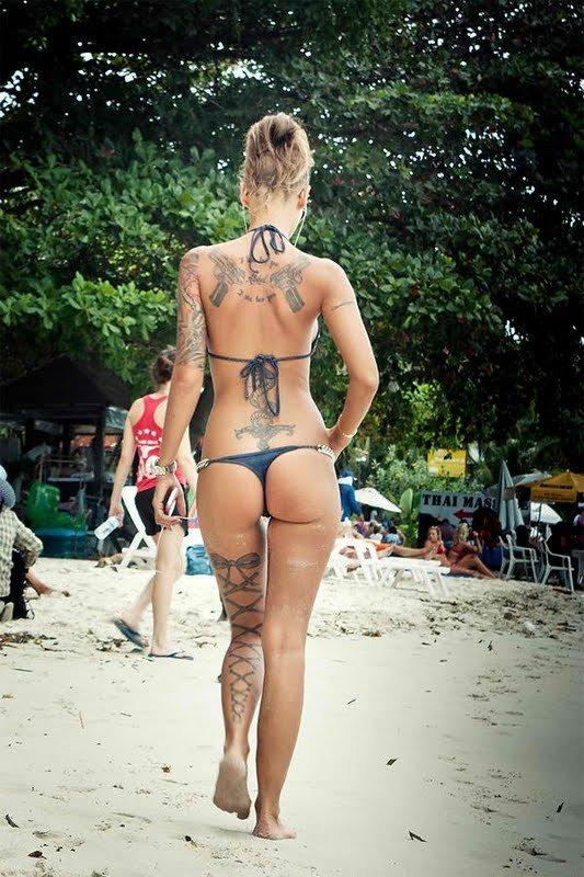 Tattooed blonde showing her nice ass in a thong bikini