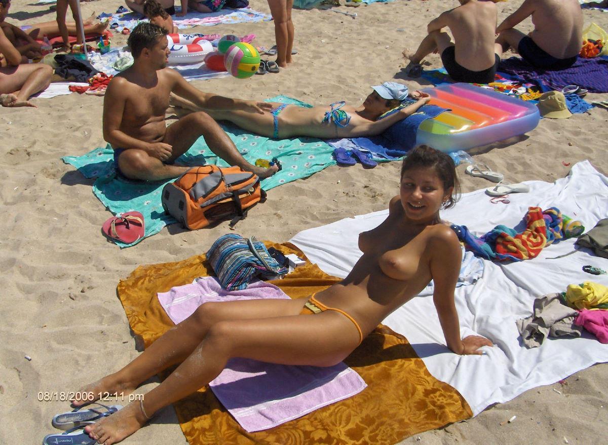 Topless cute babe preparing her boobs for tan