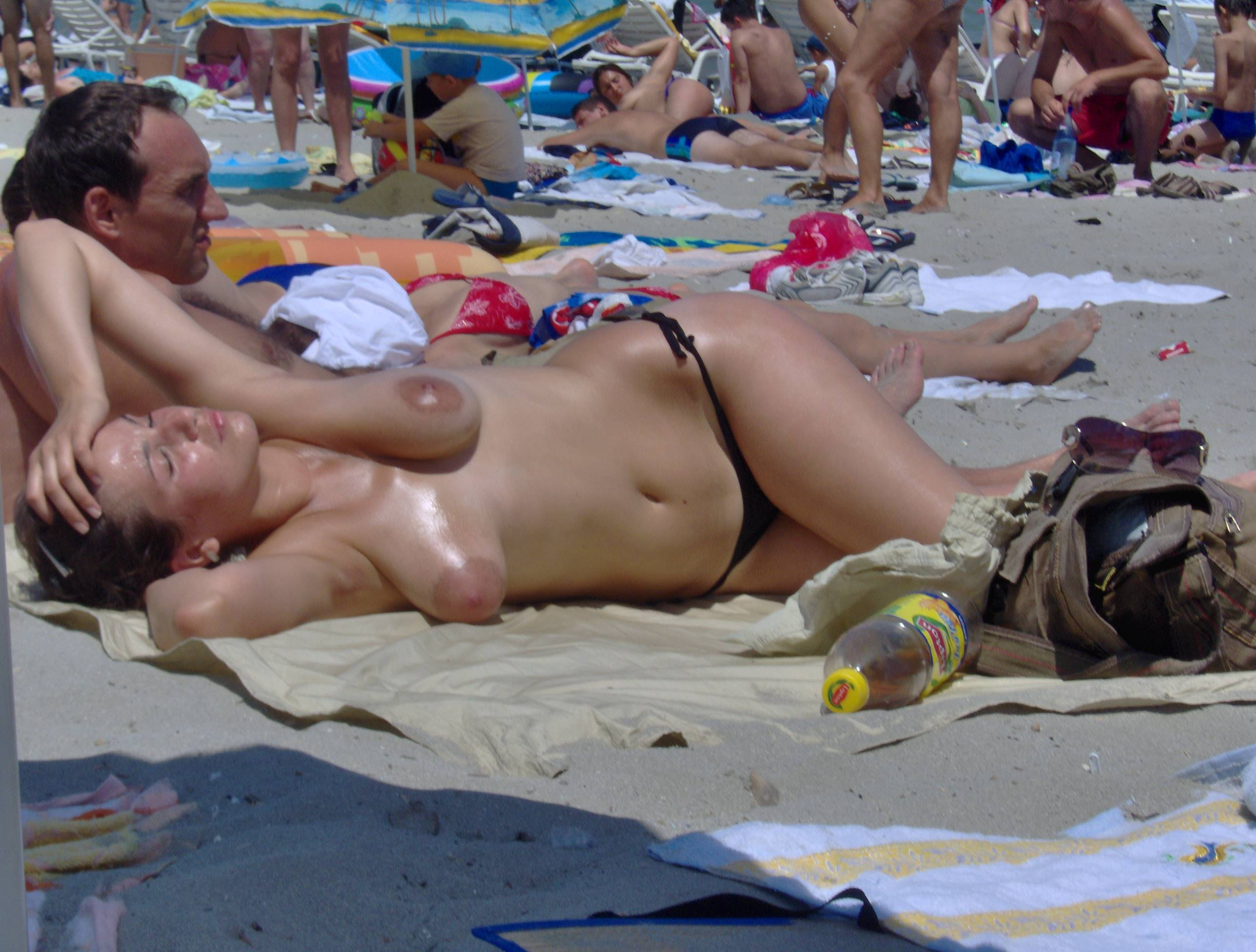Topless oiled babe tanning her boobs at beach