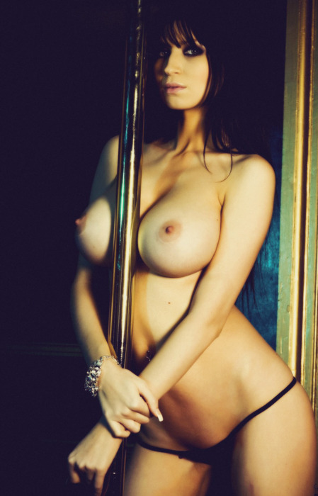 Busty brunette holding a pole in panties