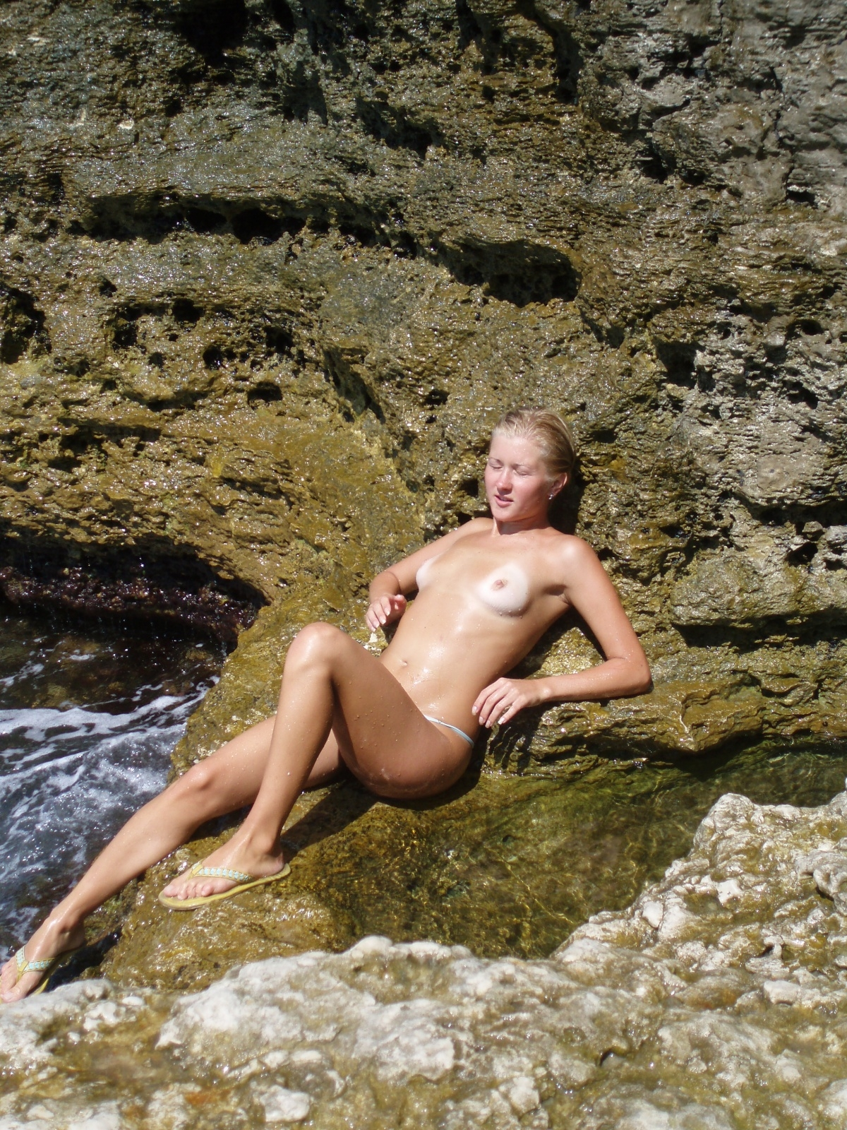 Topless sexiness tanning on a rocky beach