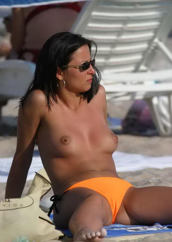 Topless babe sunbathing on nudist beach