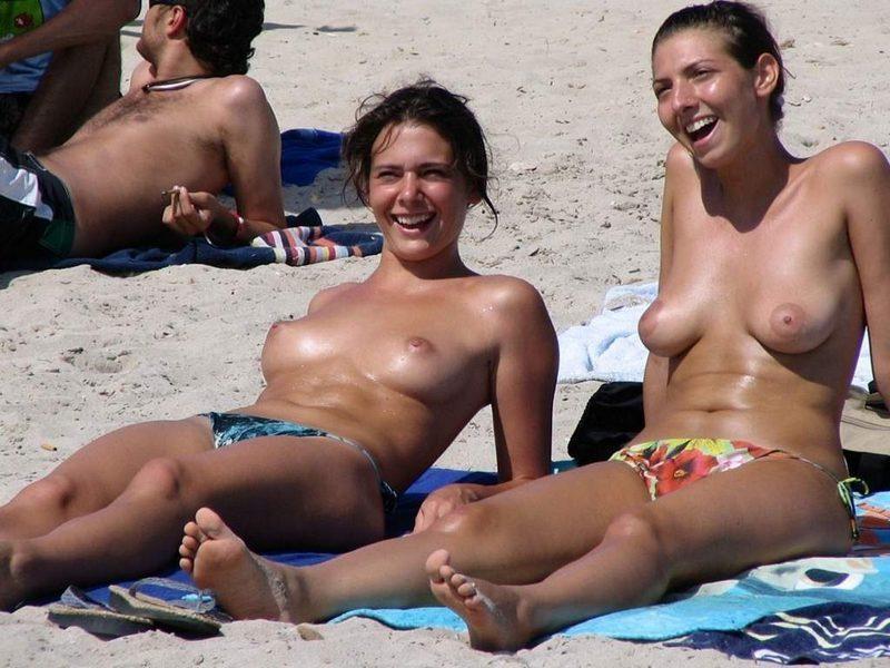 Hot topless chicks sharing a joke at the beach